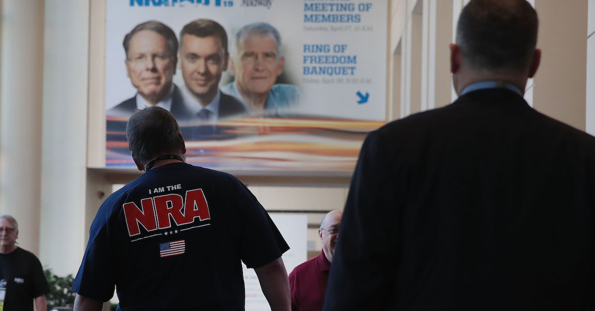 Guest walk under a poster featuring Wayne LaPierre (L), NRA vice president and CEO, Chris Cox (C), executive director of the NRA-ILA, and NRA president Oliver North outside a conference room where the NRA annual meeting of members was being held at the 148th NRA Annual Meetings