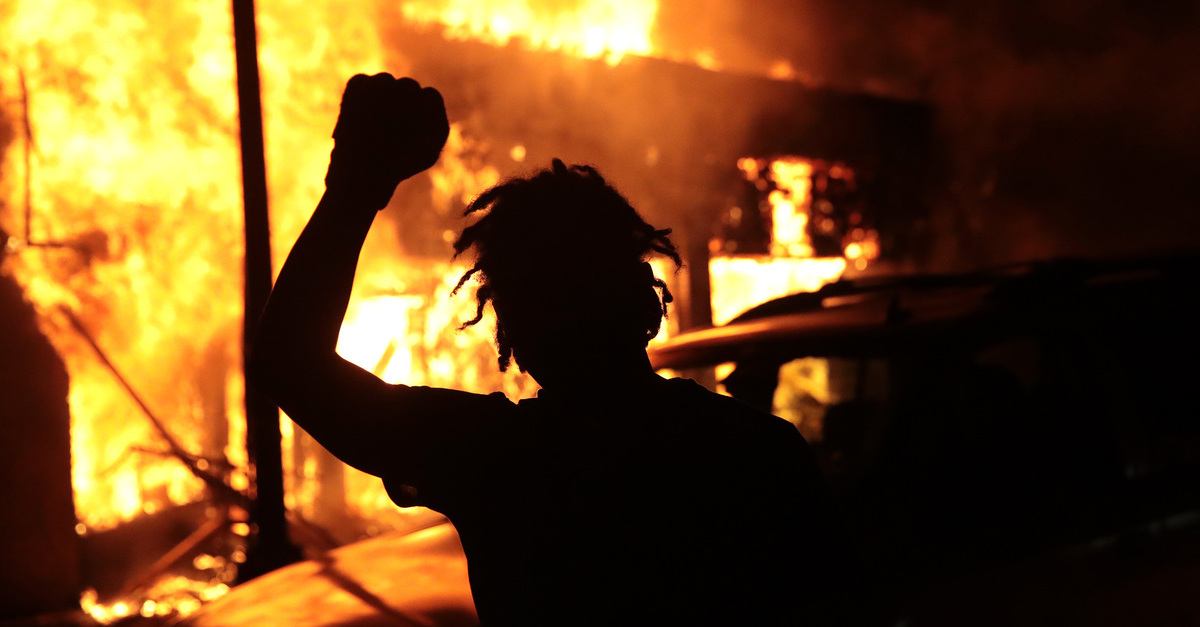 MINNEAPOLIS, MINNESOTA - MAY 29: A man raises his fist in front of a burning building during protests sparked by the death of George Floyd while in police custody on May 29, 2020 in Minneapolis, Minnesota. Earlier today, former Minneapolis police officer Derek Chauvin was taken into custody for Floyd's death. Chauvin has been accused of kneeling on Floyd's neck as he pleaded with him about not being able to breathe. Floyd was pronounced dead a short while later. Chauvin and 3 other officers, who were involved in the arrest, were fired from the police department after a video of the arrest was circulated.