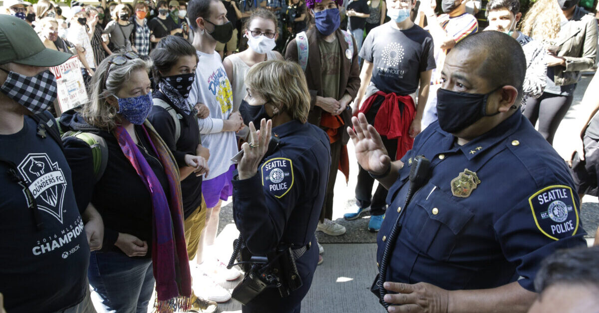 Seattle Police Assistant Chief Deanna Nollette and Assistant Chief Adrian Diaz are blocked by protesters from entering the newly created Capitol Hill Autonomous Zone (CHAZ) in Seattle, Washington on June 11, 2020. - Two police officers attempt to enter the area, but are blocked by people standing close together and holding cameras as they film. The area surrounding the East Precinct building has come to be known as the CHAZ, Capitol Hill Autonomous Zone.