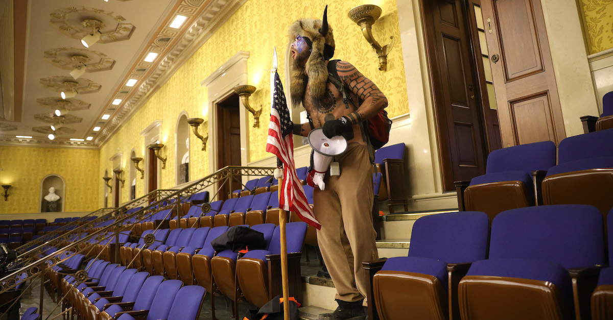 "WASHINGTON, DC - JANUARY 06: A protester screams ""Freedom"" inside the Senate chamber after the U.S. Capitol was breached by a mob during a joint session of Congress on January 06, 2021 in Washington, DC. Congress held a joint session today to ratify President-elect Joe Biden's 306-232 Electoral College win over President Donald Trump. A group of Republican senators said they would reject the Electoral College votes of several states unless Congress appointed a commission to audit the election results. Pro-Trump protesters entered the U.S. Capitol building during demonstrations in the nation's capital."