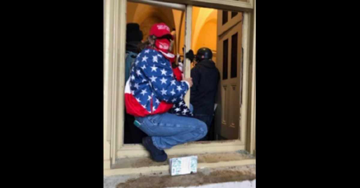 Woman identified as Jody Lynn Targaris sitting in frame of broken window. FBI says this was at the U.S. Capitol Building on January 6.