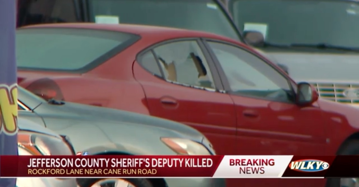 A vehicle parked in the lot Brandon Shirley was guarding appears to have had its rear passenger side window shot out.