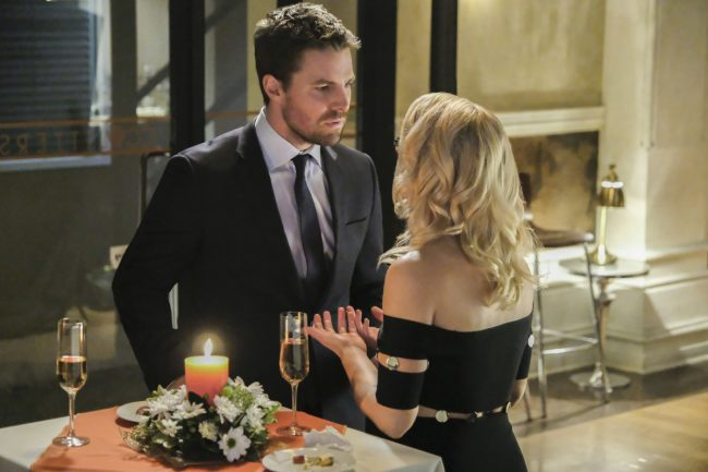 """image: Bettina Strauss/The CW Supergirl -- """"Crisis on Earth-X, Part 1"""" -- Pictured (L-R): Stephen Amell as Oliver Queen and Emily Bett Rickards as Felicity Smoak -- © 2017 The CW Network, LLC. All Rights Reserved"""