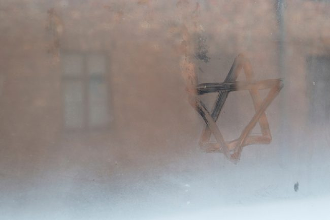 image: Brais Seara/Shutterstock Auschwitz, Lesser Poland / Poland - Feb 04 2018: Auschwitz Birkenau, Nazi concentration and extermination camp. Star of David painted by a visitor in the condensation of a window. Jewish