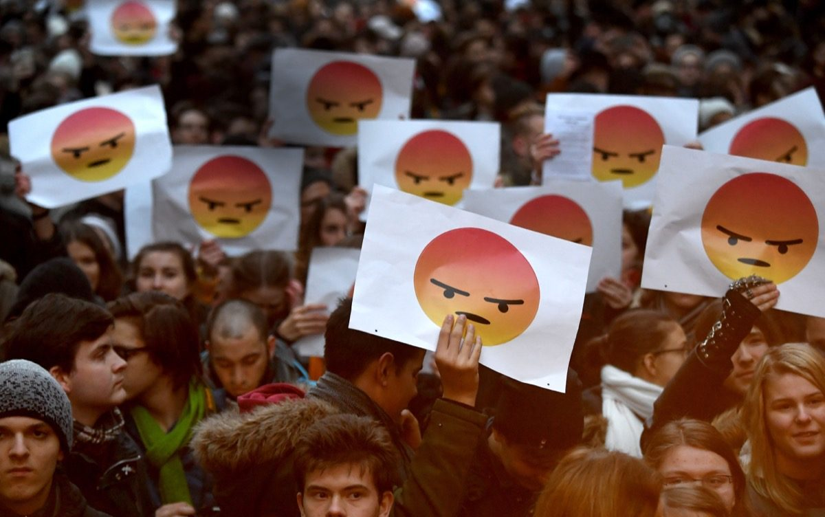 students protest with signs of angry face emoji in Hungary