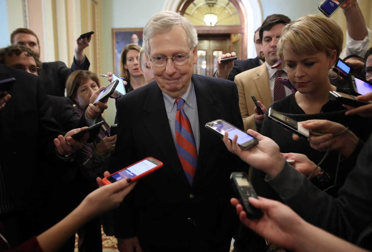 Senate Majority Leader Mitch McConnell (R-KY) smiles while talking with reporters