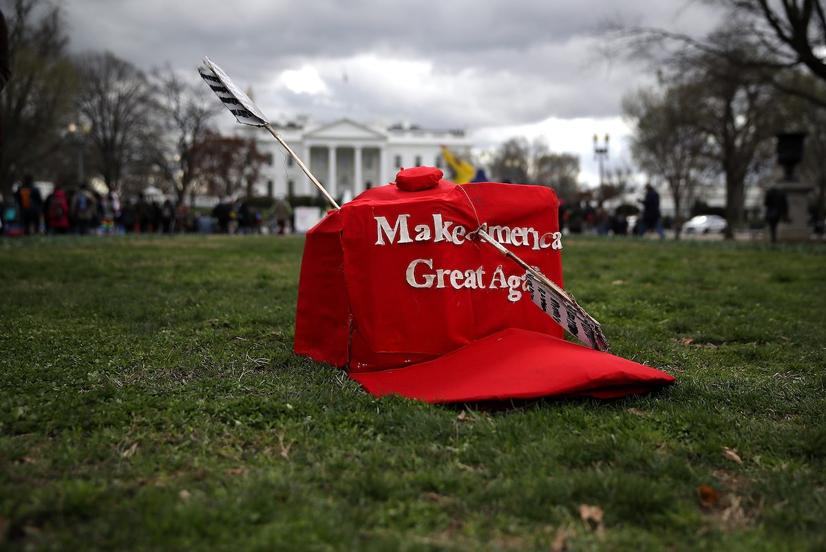 An oversized replica of a 'Make America Great Again' hat sits on the grass across from the White House during a demonstration against the Dakota Access Pipeline