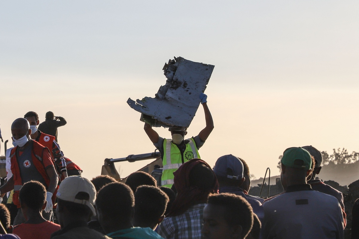 """TOPSHOT - A man carries a piece of debris on his head at the crash site of a Nairobi-bound Ethiopian Airlines flight near Bishoftu, a town some 60 kilometres southeast of Addis Ababa, Ethiopia, on March 10, 2019. - A Nairobi-bound Ethiopian Airlines Boeing crashed minutes after takeoff from Addis Ababa on March 10, killing all eight crew and 149 passengers on board, including tourists, business travellers, and """"at least a dozen"""" UN staff. (Photo by Michael TEWELDE / AFP) (Photo credit should read MICHAEL TEWELDE/AFP/Getty Images)"""