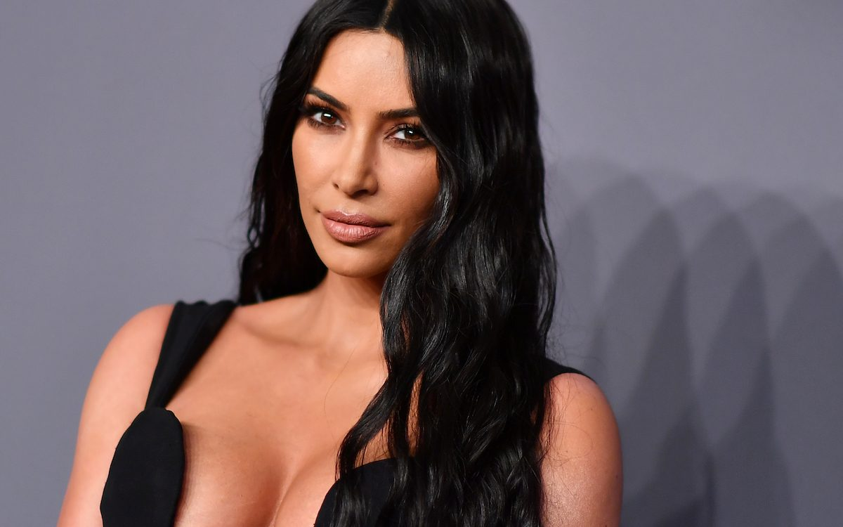Kim Kardashian in a low-cut black dress on a red carpet.