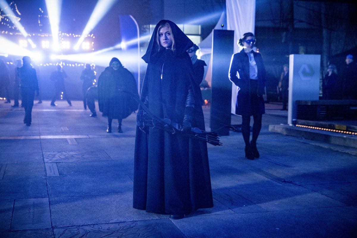Mia Smoak in a cloak, holding a bow in The CW's Arrow.
