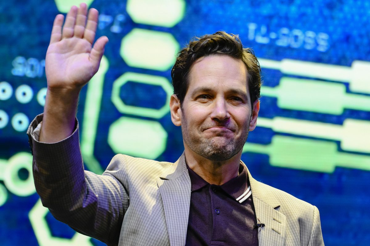 Paul Rudd waves in front of a colorful backdrop