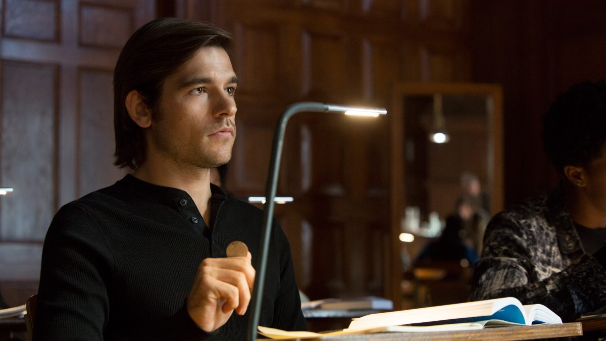 Quentin sits at a desk in Syfy's The Magicians.