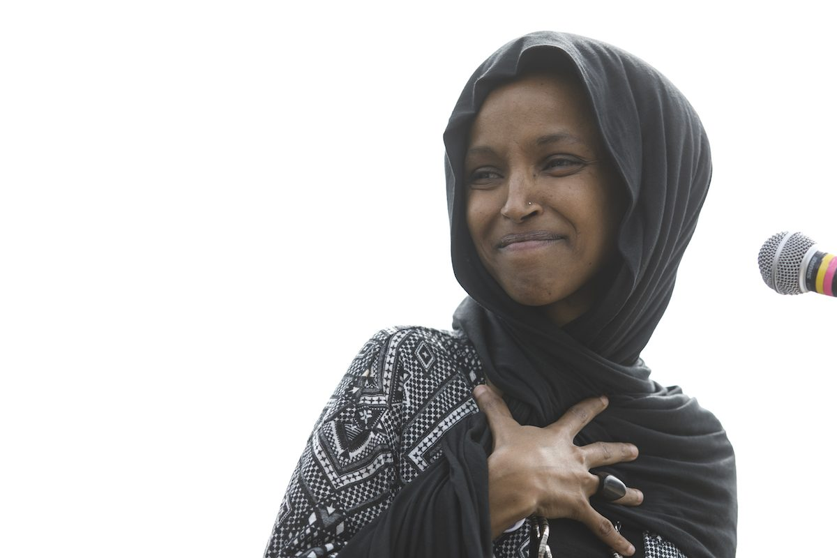 Rep. Ilhan Omar stands in front of a microphone, beaming during a climate change rally.