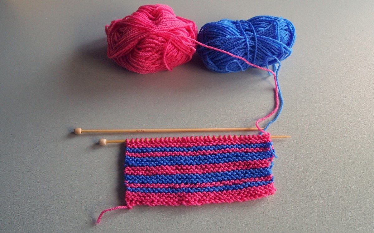 Pink and blue yarns being knit into stripes.
