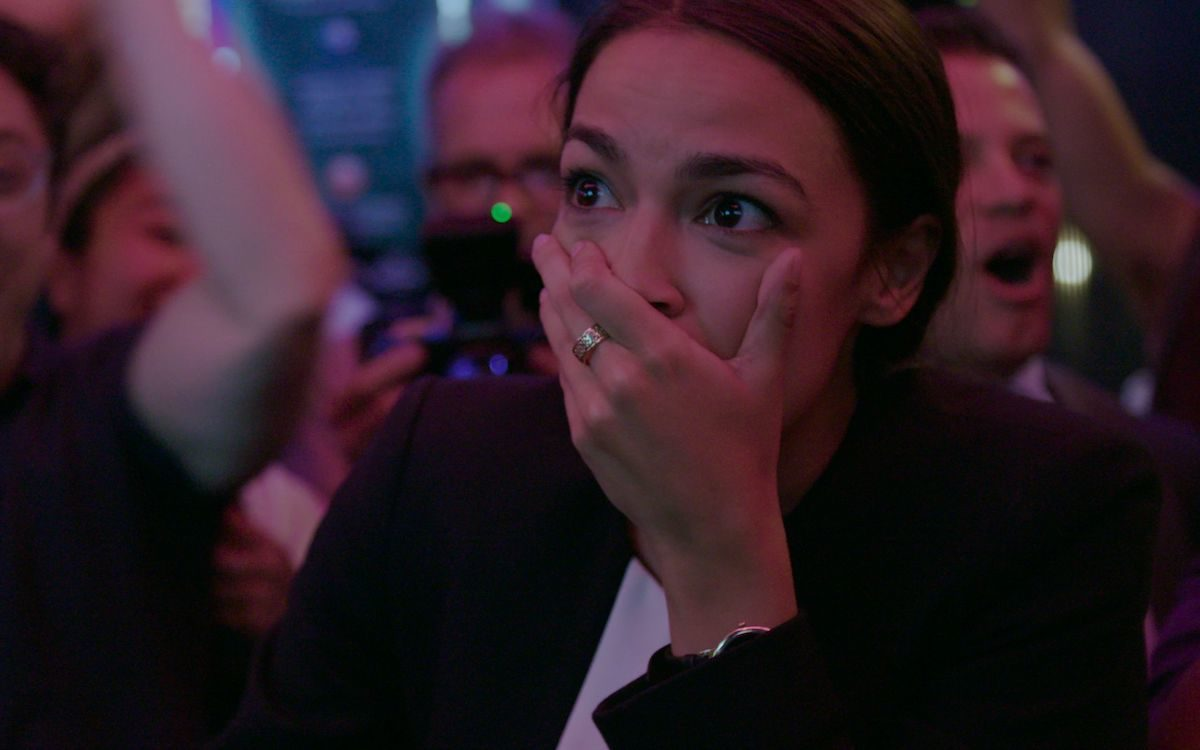 AOC covers her mouth, reacting to the news that she'd won her primary election.