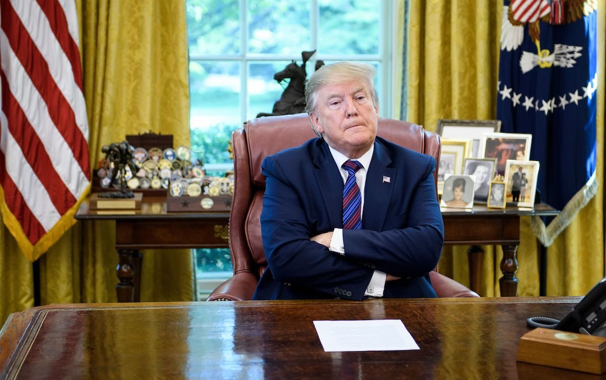 Donald Trump crosses his arms and looks pouty behind his Oval Office desk.