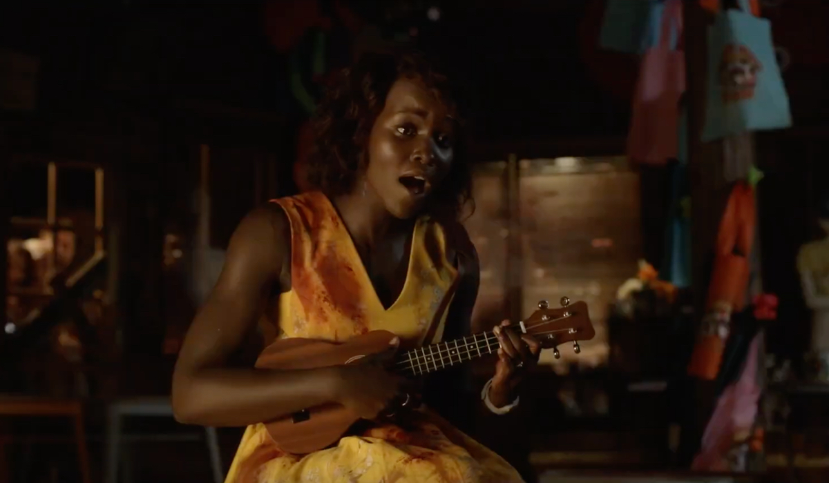 Miss Caroline (Lupita Nyong'o) keeps calm and carries on during a zombie attack in Little Monsters.