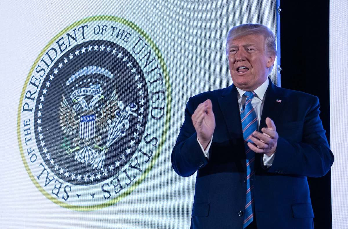 U.S. President Donald Trump stands next to a surreptitiously altered presidential seal as he arrives to address the Turning Point USAs Teen Student Action Summit.