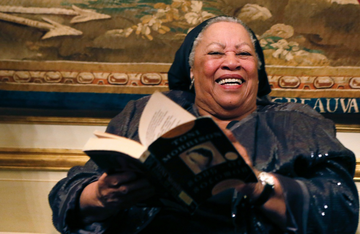 """US author Toni Morrison (C) poses with her 1977 novel entitled """"Song of Solomon"""" on September 21, 2012 during a reception sponsored by the US ambassador Charles H. Rivkin (R) at his residence in Paris, as part of the 10th America Festival. The America Festival is a cultural event held in France every two years which gathers well-known figures from the world of literature, music and cinema. AFP PHOTO / PATRICK KOVARIK (Photo credit should read PATRICK KOVARIK/AFP/GettyImages)"""
