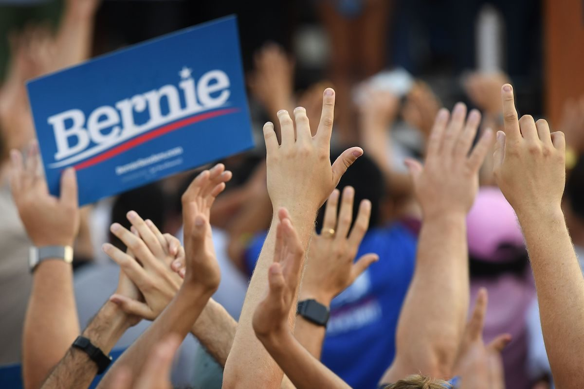 People cheer as 2020 Democratic presidential hopeful Vermont US Senator Bernie Sanders (off frame) arrives to speak to a crowd of supporters during a campaign rally