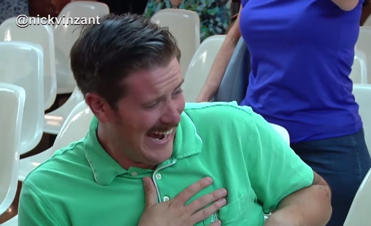 A man in a green shirts laughing.