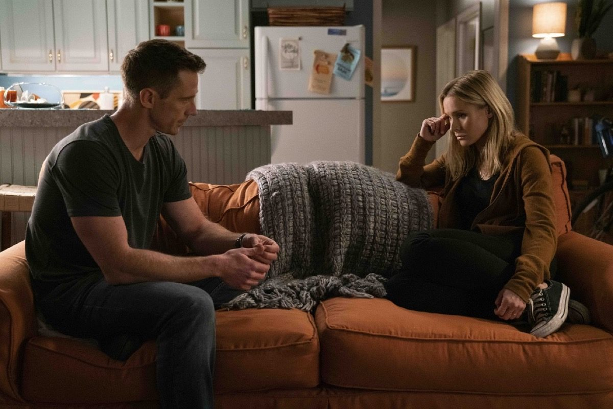 Veronica and Logan on the couch looking at each other with angst in Hulu's Veronica Mars season 4.