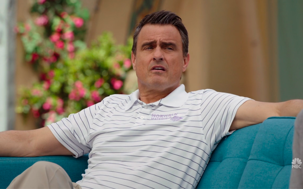 The Good Place's Brent leans back on a sofa with a smug look.