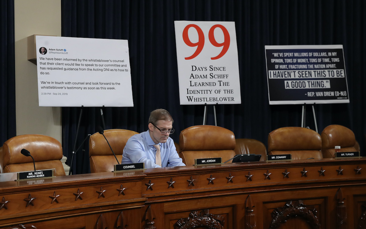 Rep. Jim Jordan sits alone in a Capitol Hill hearing room in front of a bunch of stupid giant signs.