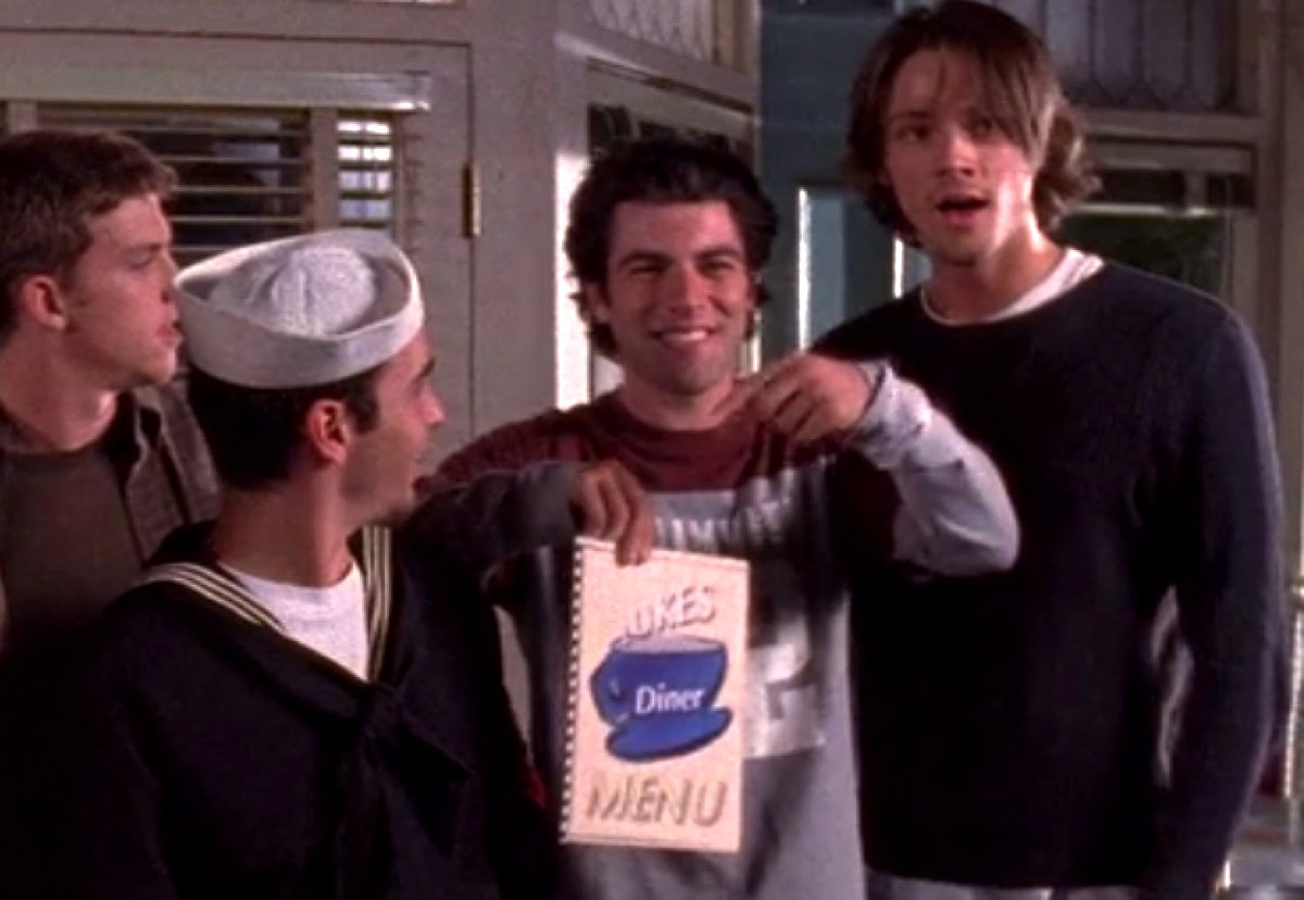 """Max Greenfield holding up a """"Luke's"""" menu on Gilmore Girls."""