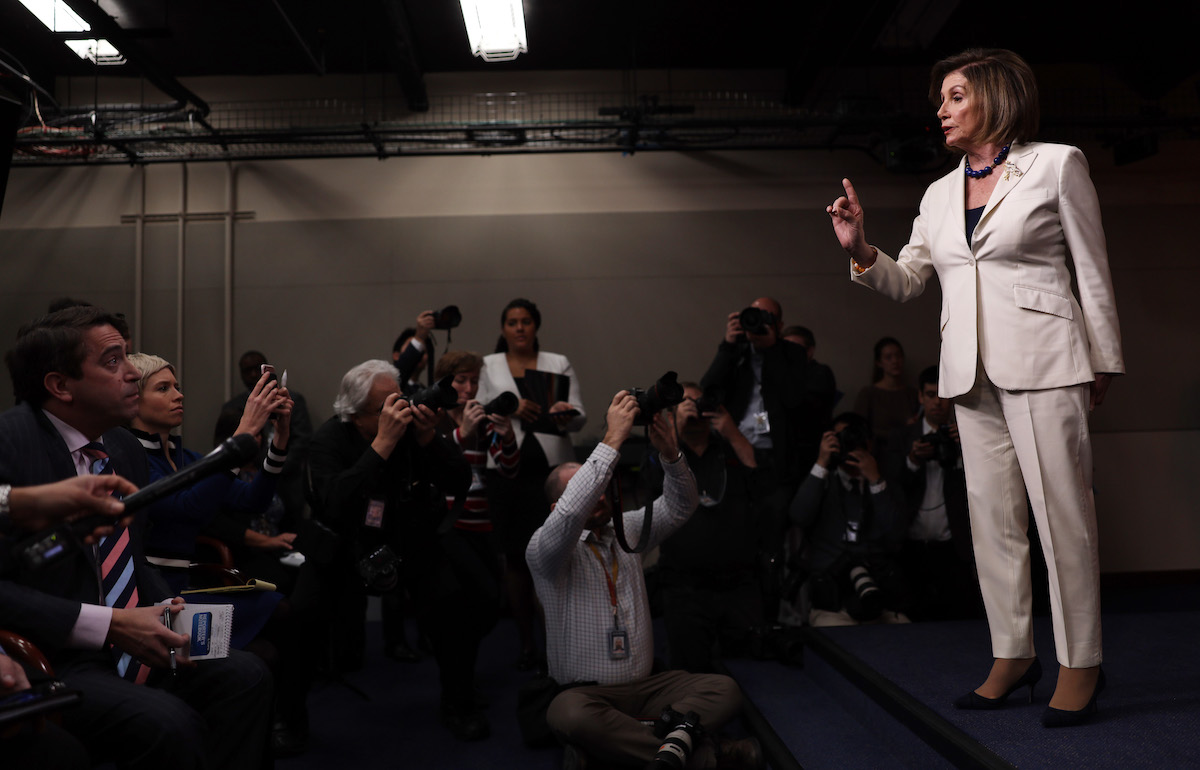 U.S. Speaker of the House Rep. Nancy Pelosi (D-CA) reacts to a reporter's (L) question about whether she hates President Donald Trump during her weekly news conference