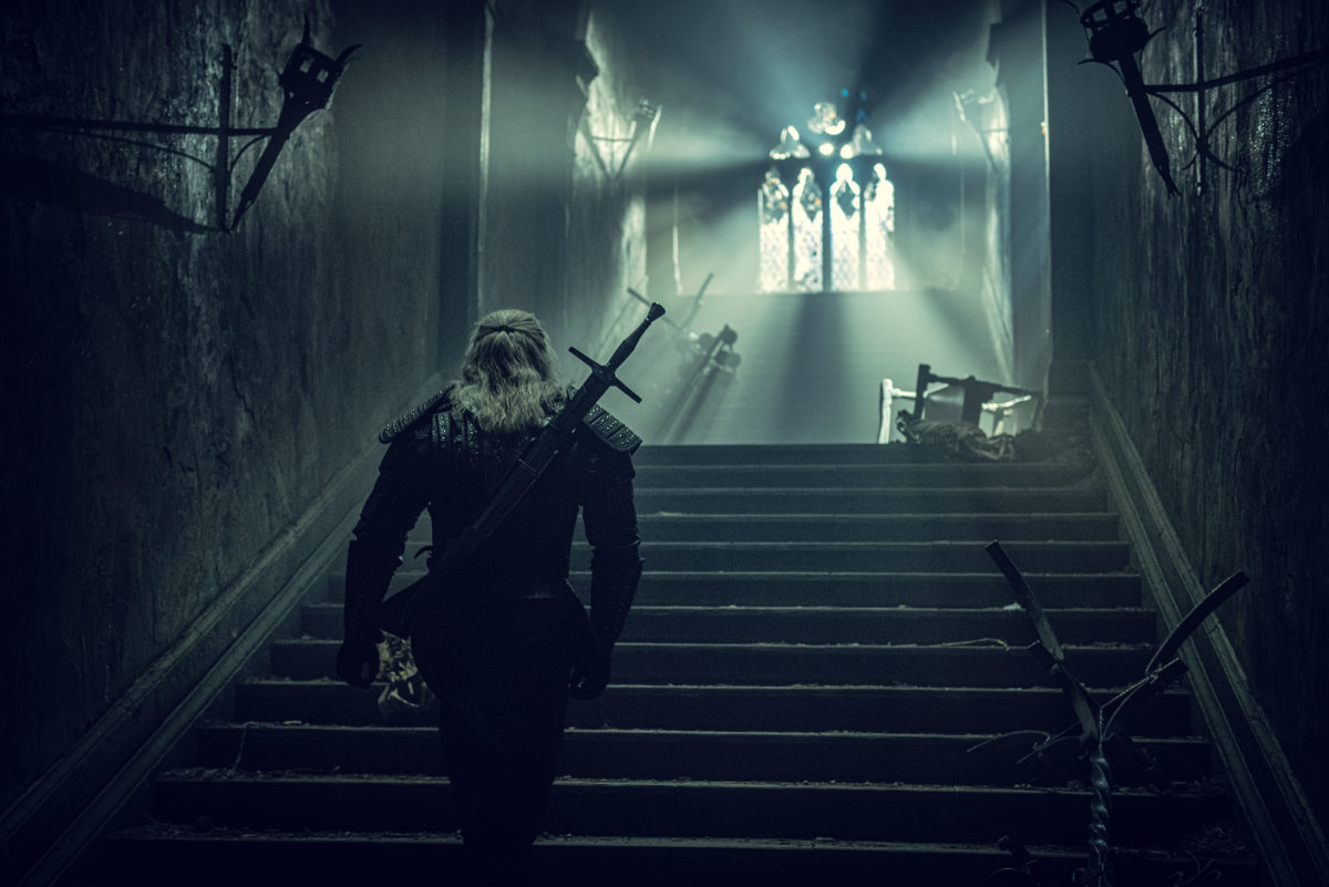 Henry cavil and gerralt walks up spooky stairs in The Witcher.