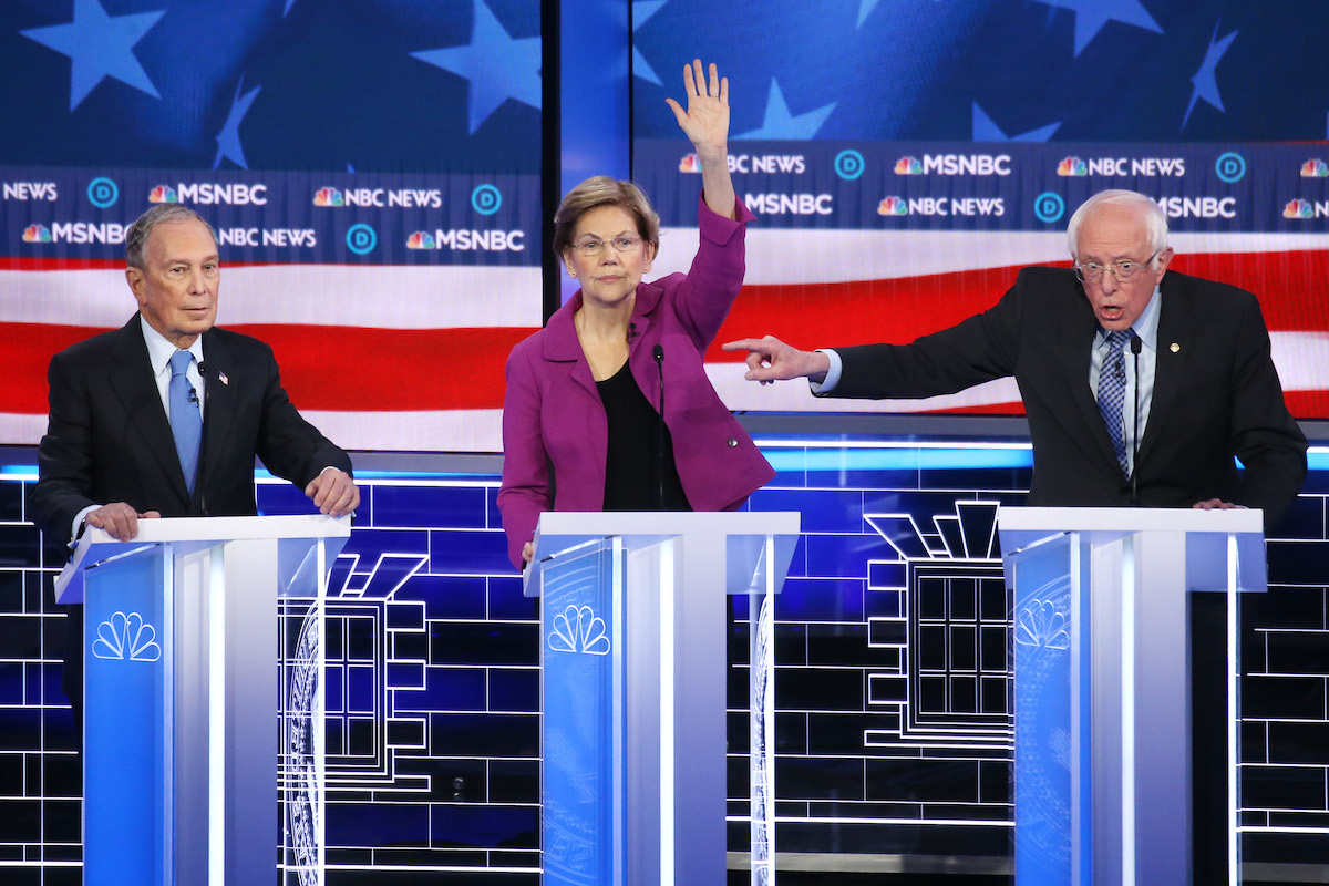 Democratic presidential candidate Sen. Bernie Sanders (I-VT) (R) gestures as Sen. Elizabeth Warren (D-MA) raises her hand and former New York City mayor Mike Bloomberg listen during the Democratic presidential primary debate