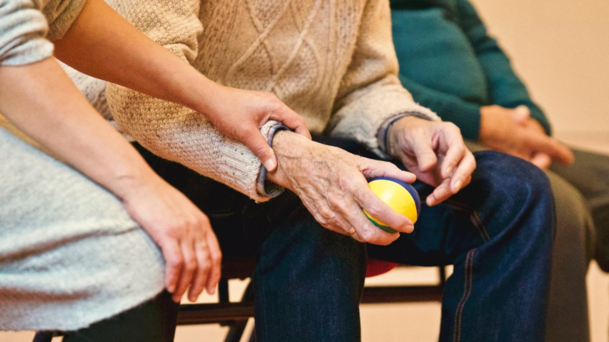 a younger person holds and elderly person's hands