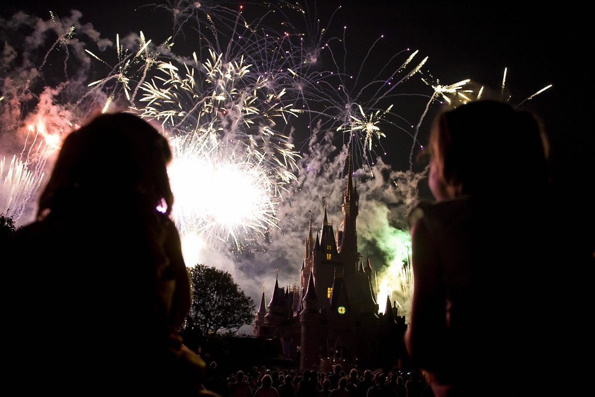 Two children watch the fireworks display as it explodes over Cinderella's Castle at Disney World's Magic Kingdom in Orlando, Florida, May 7, 2008. The complex is reportedly the most visited and largest recreational resort in the world, containing four theme parks, two water parks, twenty-three themed hotels, and numerous shopping, dining, entertainment and recreation venues. Disney World opened on October 1, 1971. AFP PHOTO/Jim WATSON (Photo credit should read JIM WATSON/AFP via Getty Images)