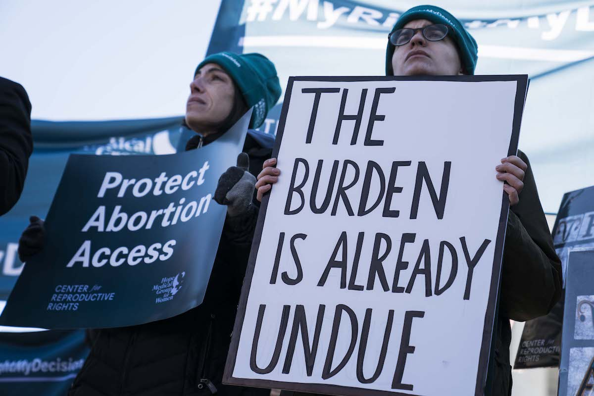 """Abortion rights demonstrators hold pro-choice sign reading """"the burden is already undue"""""""