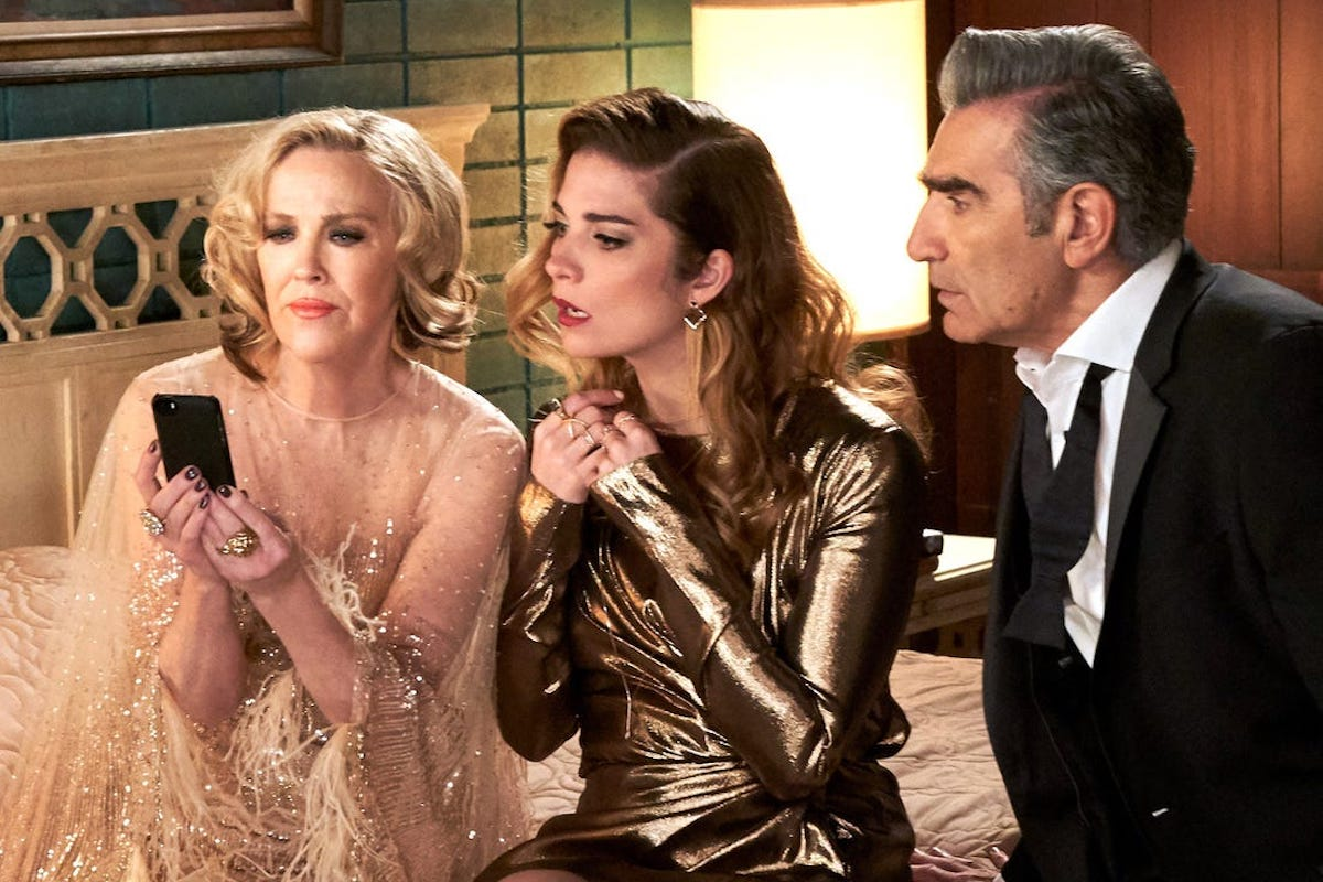 Schitt's Creek's Moira, Alexis, and Johnny look at a cell phone.