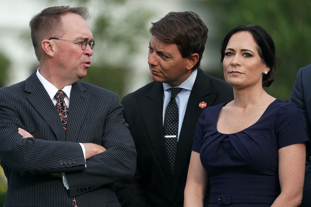 Stephanie Grisham stares at the camera while two men talk