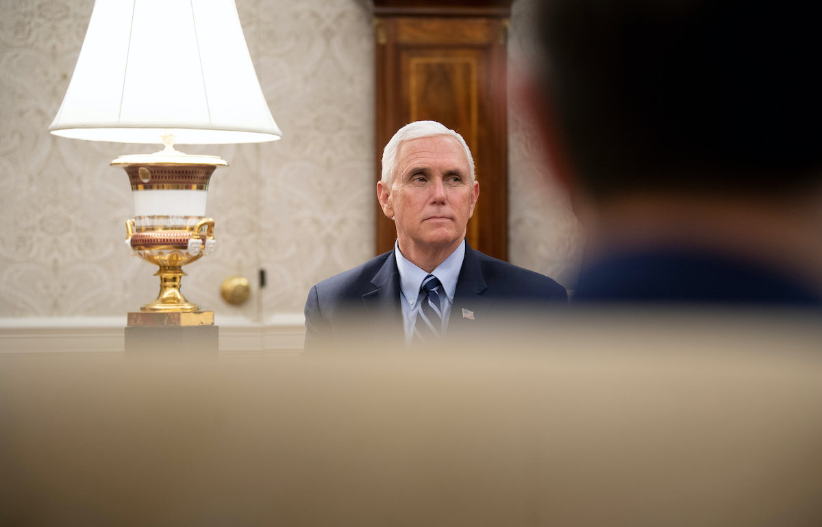 Mike Pence sits in the Oval Office without a face mask.