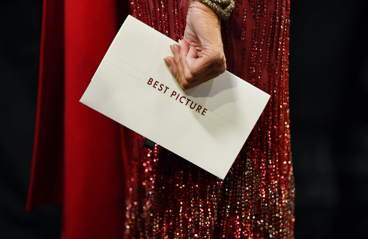 A woman's hand holds the Best Picture envelope