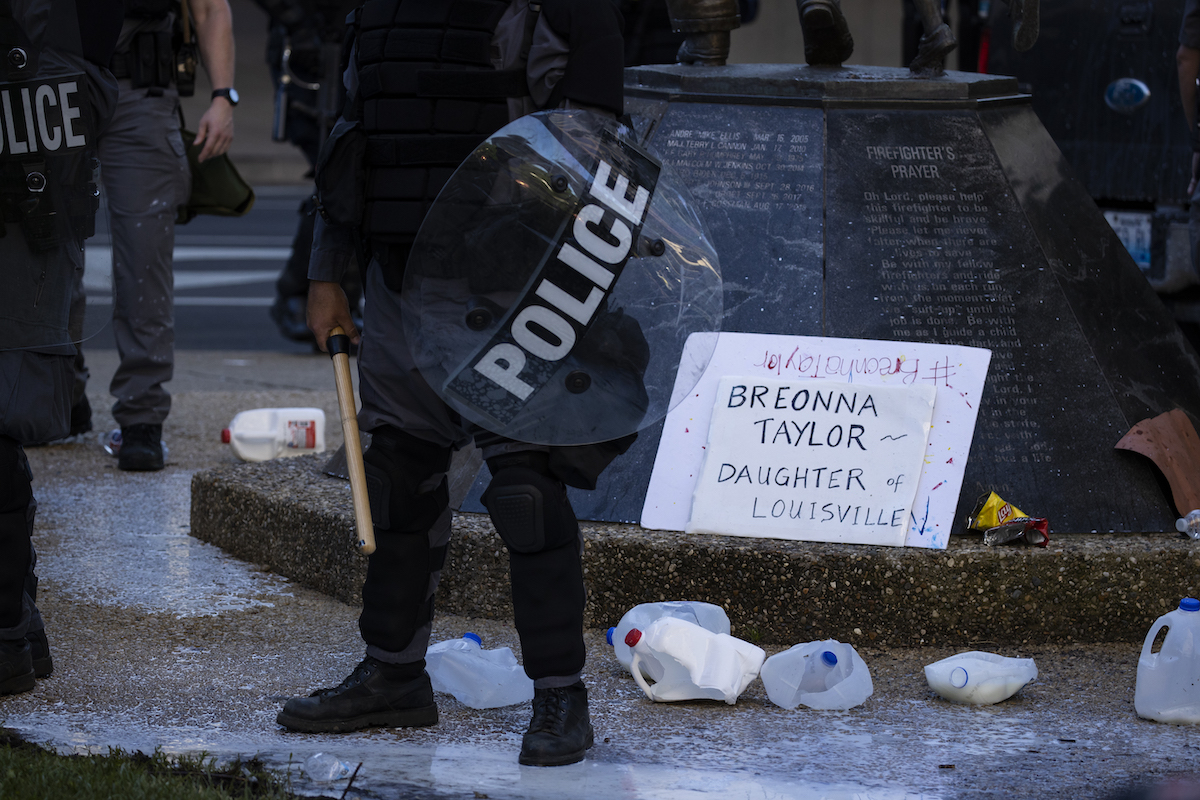 Police officers in riot gear stand in and around milk jugs and a sign honoring Breonna Taylor.