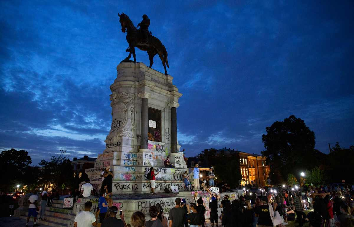 People gather around the Robert E. Lee statue on Monument Avenue in Richmond, Virginia