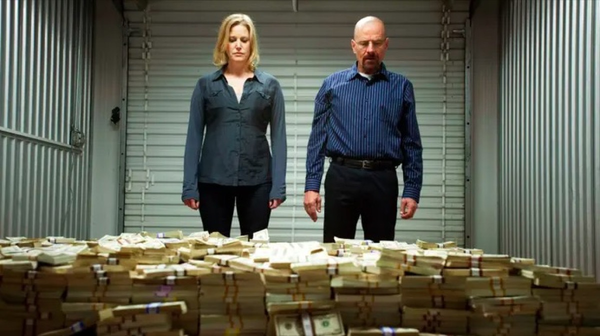 Skyler and Walter White staring at a massive pile of money in a storage unit on AMC's Breaking Bad.