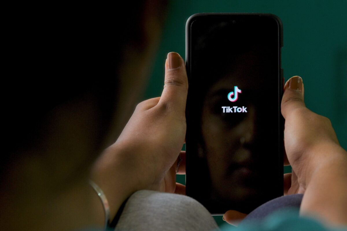 """An Indian mobile user browses through the Chinese owned video-sharing 'Tik Tok' app on a smartphone in Bangalore on June 30, 2020. - TikTok on June 30 denied sharing information on Indian users with the Chinese government after New Delhi banned the wildly popular app citing national security and privacy concerns. """"TikTok continues to comply with all data privacy and security requirements under Indian law and have not shared any information of their users in India with any foreign government, including the Chinese Government,"""" said the company, which is owned by China's ByteDance. (Photo by Manjunath Kiran / AFP) (Photo by MANJUNATH KIRAN/AFP via Getty Images)"""