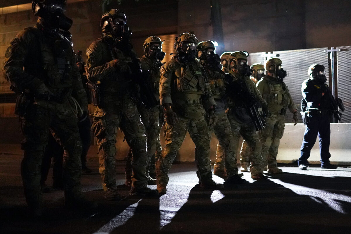 PORTLAND, OR - JULY 30: Federal officers form a police line in front of the Mark O. Hatfield U.S. Courthouse in the early hours of July 30, 2020 in Portland, Oregon. Protests against the federal presence in Portland continued Wednesday following an announcement by Governor Kate Brown that federal officers would begin a phased withdrawal from the city. (Photo by Nathan Howard/Getty Images)