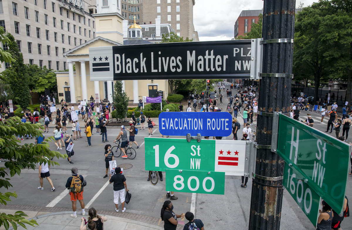 "People walk near 16th and H street after volunteers, with permission from the city, painted ""Black Lives Matter"" on the street near the White House"