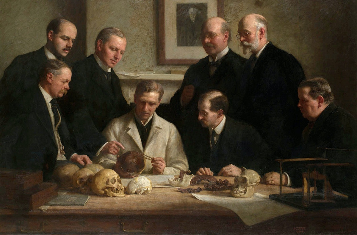 Group portrait of the Piltdown skull being examined. Back row (from left): F. O. Barlow, G. Elliot Smith, Charles Dawson, Arthur Smith Woodward. Front row: A. S. Underwood, Arthur Keith, W. P. Pycraft, and Ray Lankester. Note the portrait of Charles Darwin on the wall. Painting by John Cooke, 1915.