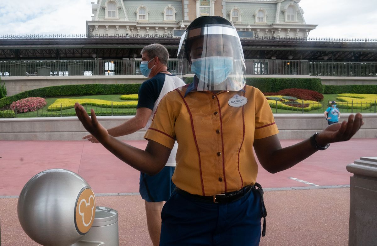 An employee at Walt Disney World Resort's Magic Kingdom wears a facemask and face shield at the entrance to the park