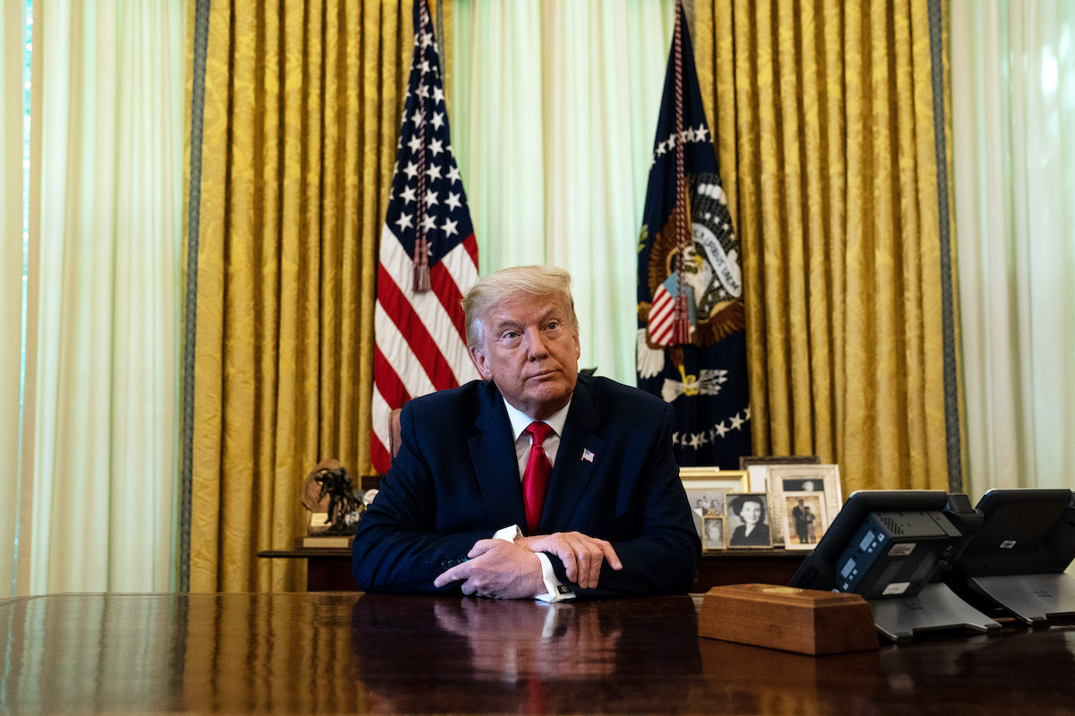 Donald Trump sits at his Oval Office desk.
