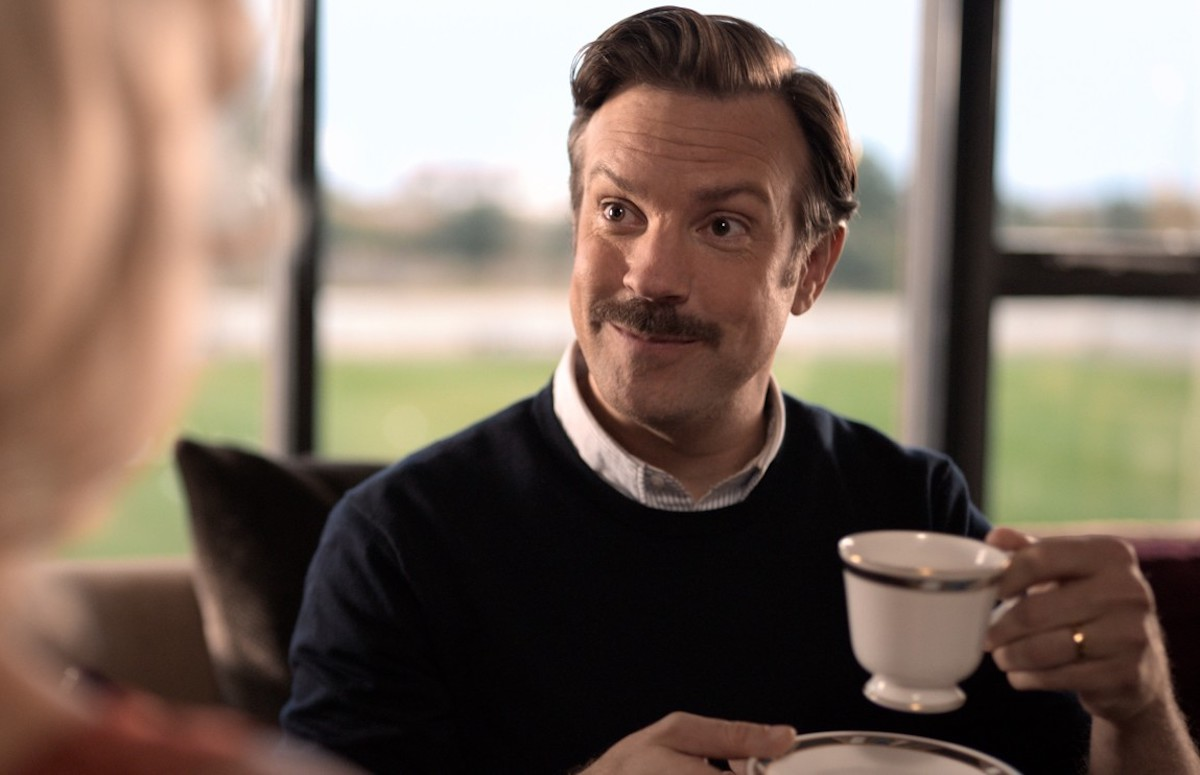 Ted Lasso holds a cup of tea.