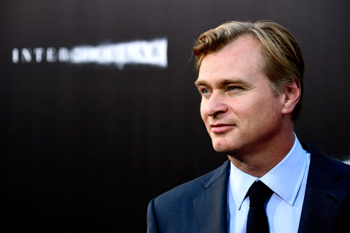 Christopher Nolan stands in front of a marketing background for Interstellar.